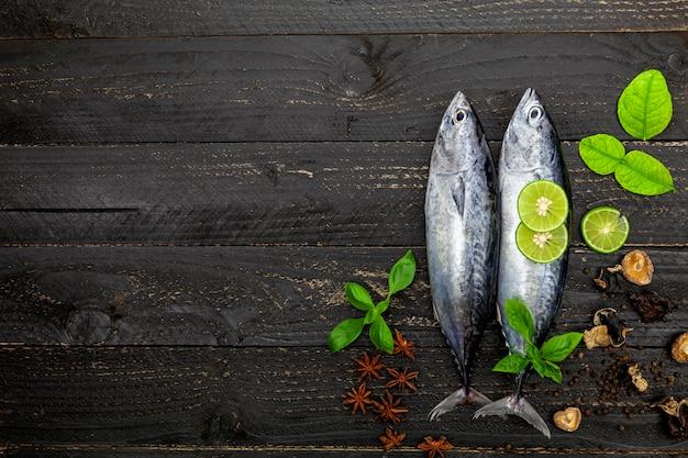 Poisson thon frais sur fond en bois noir foncé, poisson avec des épices et des légumes Photo Premium
