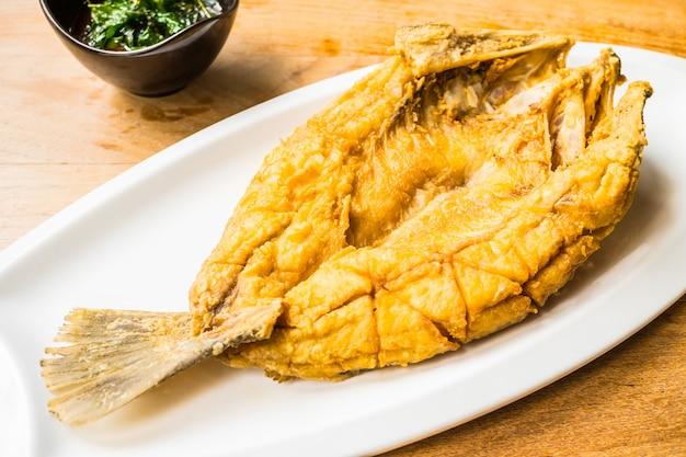 Poissons de bar frits dans une assiette blanche avec une sauce épicée et sucrée Photo gratuit