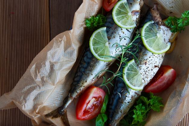Poissons de mer entiers cuits au four sur du papier sulfurisé au citron et aux herbes. Photo Premium