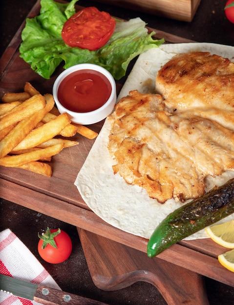 Poitrine de poulet au four avec frites au lavash avec légumes et ketchup sur planche de bois Photo gratuit