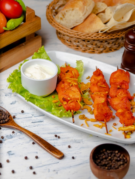 Poitrine de poulet barbecue, shish kebab avec des légumes, des herbes et du sumakh et yogourt en plaque blanche. Photo gratuit