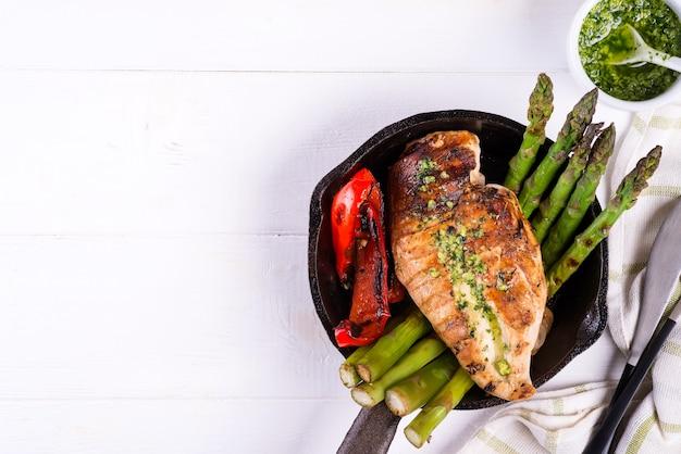 Poitrine de poulet grillade avec légumes barbecue et sauce pesto dans une poêle en fonte sur fond blanc Photo Premium