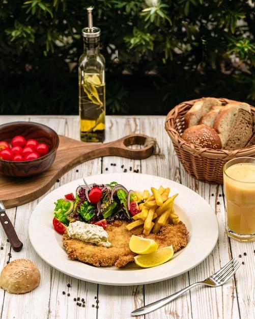 Poitrine de poulet servie avec frites et légumes Photo gratuit