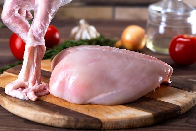 Poitrines De Poulet Crues Sur Une Planche à Découper Avec La Peau Photo Premium