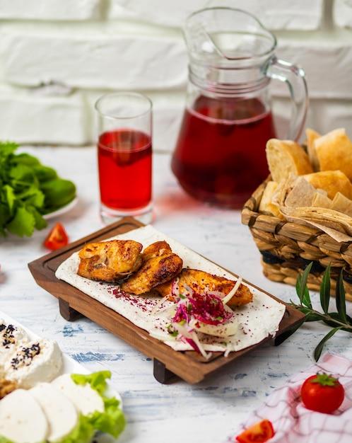Poitrines de poulet saines marinées, grillées, cuites sur un barbecue estival et servies à la lavash avec des herbes fraîches, du vin, du pain sur une planche de bois, vue rapprochée Photo gratuit
