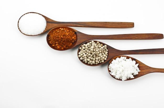 Poivre de cayenne, sel, sucre, grain de poivre sur une cuillère en bois Photo Premium