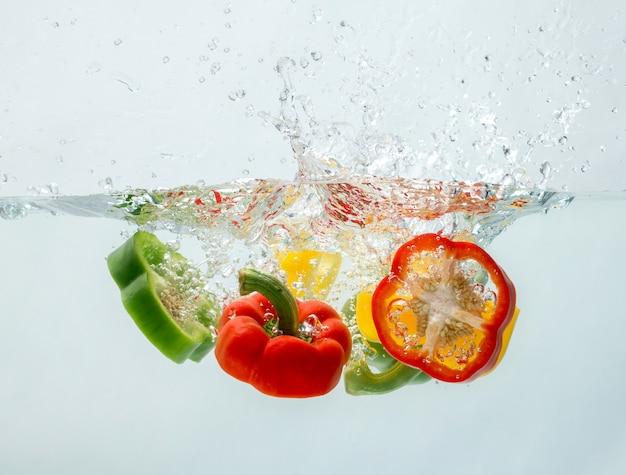 Poivrons qui tombent dans l'eau ont l'air si frais. Photo Premium