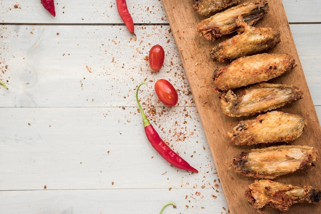 Poivrons et tomates près des ailes de poulet Photo gratuit