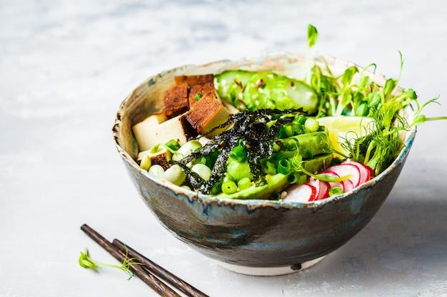 Poke bol avec avocat, riz noir, tofu fumé, haricots, légumes, choux Photo Premium