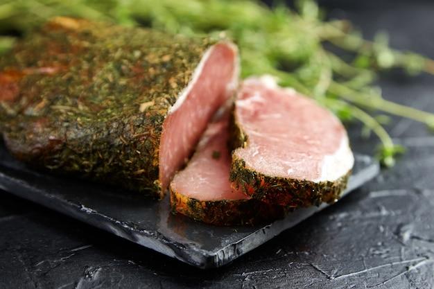 Polendwitz Est Un Filet Séché, Porc Séché Aux épices Et Thym Vert Frais, Planche à Découper En Ardoise Sur Tableau Noir Photo Premium