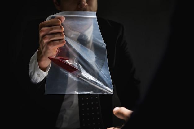 La police dans la salle d'interrogatoire montrant un couteau comme preuve de meurtre Photo Premium
