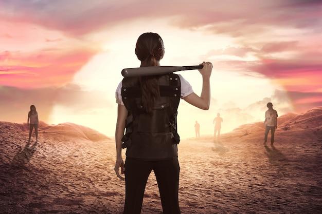 Police femme asiatique avec une batte de baseball à l'épaule, regardant les zombies Photo Premium