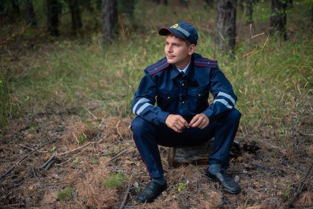 Un policier est assis sur l'herbe dans la forêt et pense Photo Premium