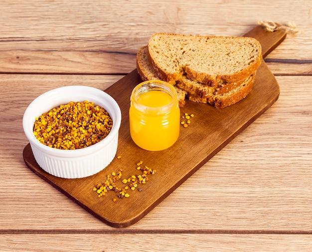 Pollen d'abeille avec du miel et du pain sur une planche à découper en bois sur le bureau Photo gratuit