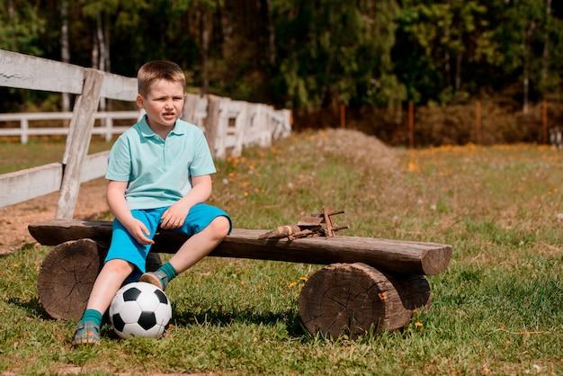 Une pom-pom girl garçon est assise avec un ballon de football sur le terrain en train de regarder le football. Photo Premium