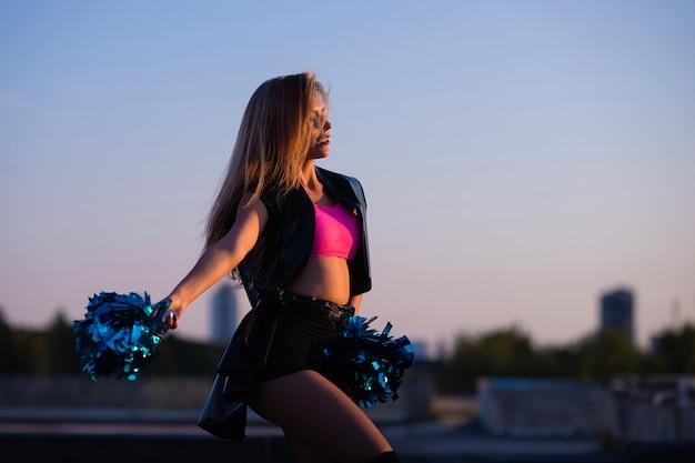 Pom-pom girl à pompons dansant en plein air sur le toit au coucher du soleil Photo Premium