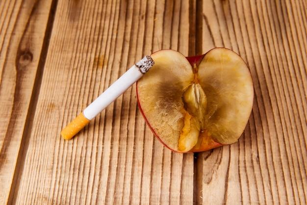 La pomme flétrie et les cigarettes représentent une mauvaise influence. Photo Premium