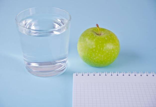 Pomme fraîche, verre d'eau et carnet de notes sur bleu Photo Premium