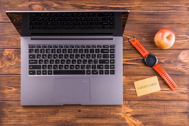 Pomme; montre-bracelet; ordinateur portable et carte d'or sur le bureau en bois Photo gratuit