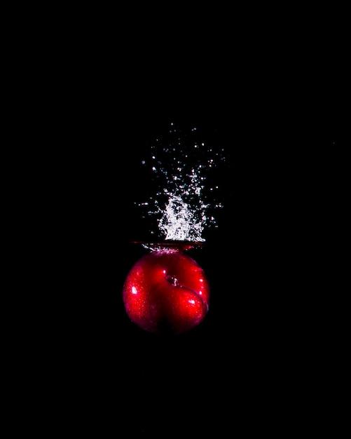 Pomme plongeant dans l'eau Photo gratuit