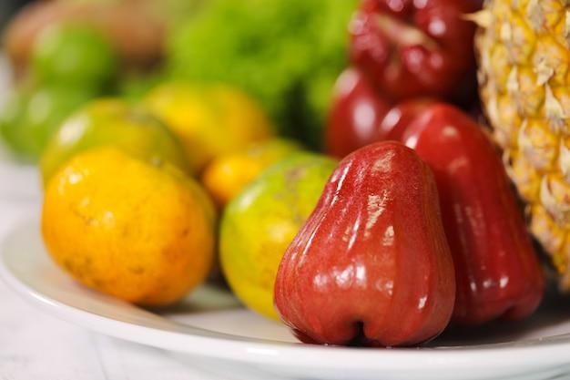 Pomme rose et orange sur une plaque blanche. Photo Premium