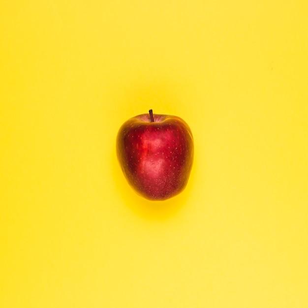 Pomme rouge juteuse mûre sur une surface jaune Photo gratuit