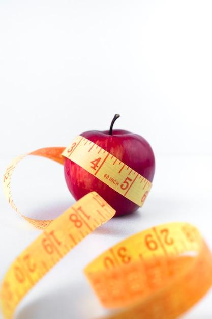 Pomme rouge avec ruban à mesurer sur une table blanche Photo gratuit