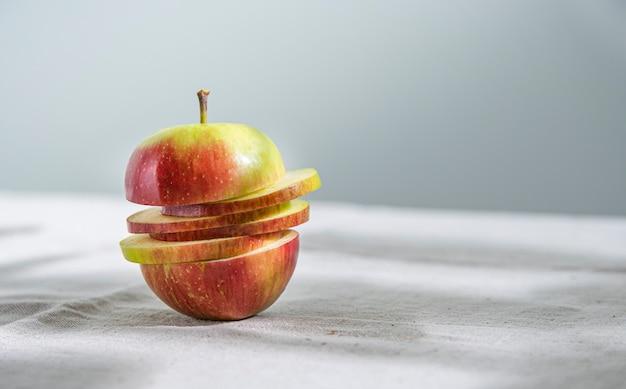 Pomme Rouge Verte Juteuse Coupée En Tranches Sur Une Nappe En Lin Naturel. Vue De Face Et Gros Plan. Orientation Horizontale Photo Premium