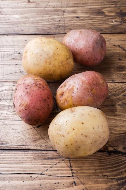 Pomme de terre crue rouge et jaune. pommes de terre fraîches sur la table en bois Photo Premium
