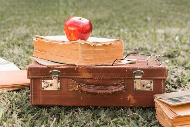 Pomme et verres sur le livre et la valise Photo gratuit