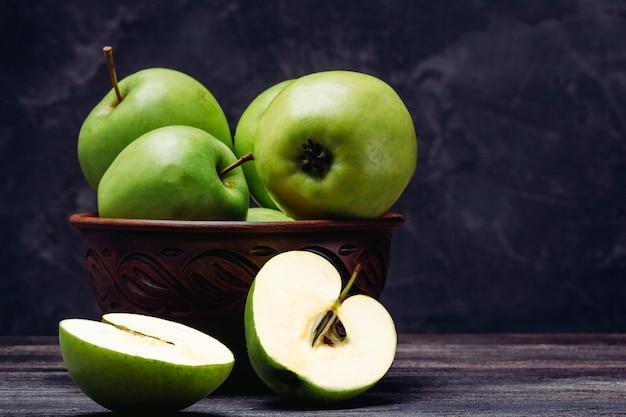 Une Pomme Verte Coupée En Deux à Côté D'un Bol Rempli De Pommes Photo Premium