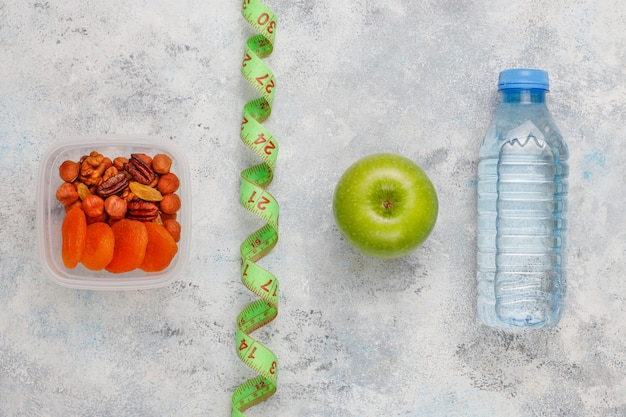 Pomme Verte Fraîche, Ruban à Mesurer Et Bouteille D'eau Fraîche Sur Béton Gris Photo gratuit