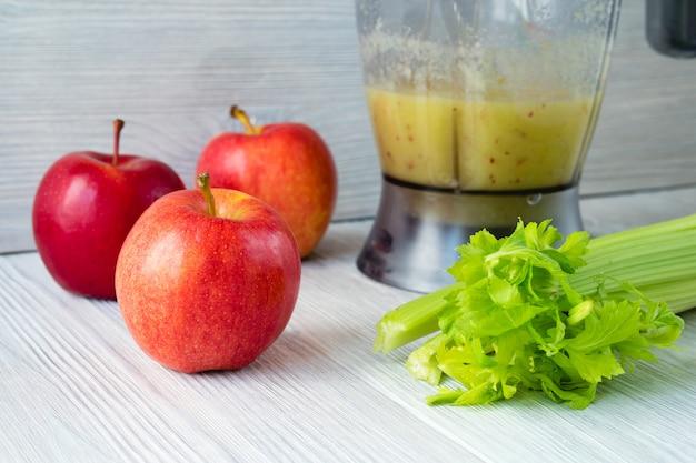 Des pommes et un bouquet de céleri et un robot culinaire avec un smoothie sur une table blanche Photo Premium