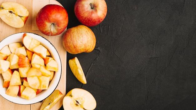 Des pommes coupées et entières sur une planche à découper Photo gratuit
