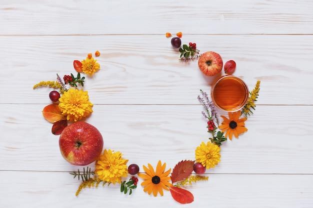 Des pommes, des fleurs et du miel avec espace copie forment une décoration florale Photo Premium