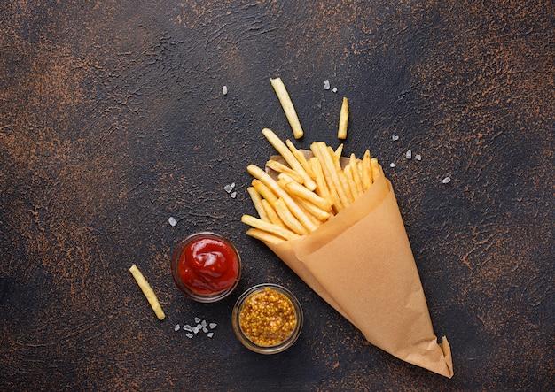 Pommes frites dans un sac en papier avec des sauces Photo Premium