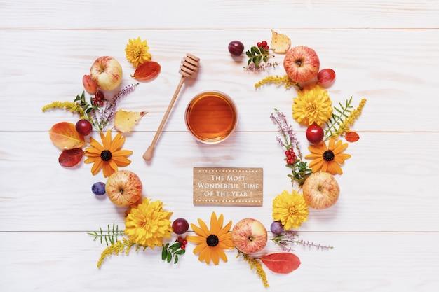 Pommes, miel, prunes, baies rouges et belles fleurs Photo Premium