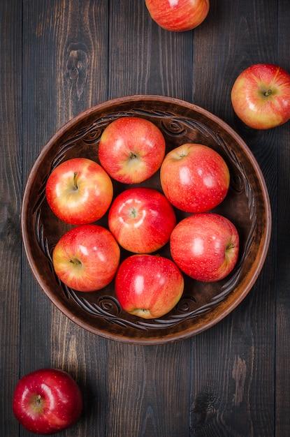 Pommes rouges sur un fond rustique foncé dans un bol en argile. lay plat. Photo Premium