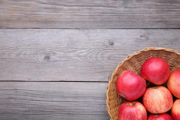 Pommes rouges fraîches sur fond en bois. pommes rouges fraîches dans un panier Photo Premium