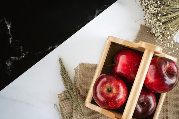 Pommes Rouges Juteuses Fraîches Dans Un Panier En Bois Sur Un Sac Et Une Surface En Marbre Noir Et Blanc Avec De L'herbe De Blé Et Un Bouquet De Fleurs D'herbe Photo Premium