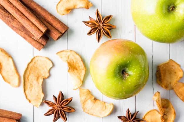 Pommes séchées bâtonnets de pomme à la cannelle pommes vertes mûres anis étoilé sur la table Photo Premium
