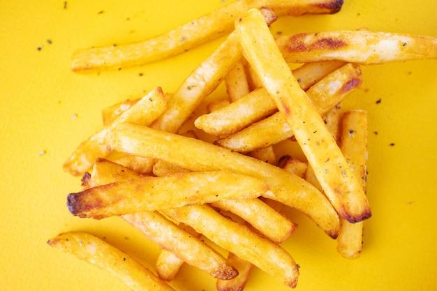 Pommes de terre au four avec des herbes aromatiques sur un fond jaune. Photo Premium