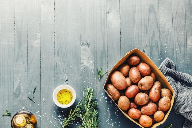 Pommes de terre biologiques brutes aux épices sur la surface de la table en bois Photo gratuit