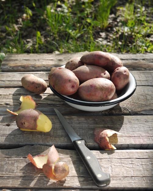 Pommes de terre fraîches dans une assiette sur une table en bois dans la nature Photo Premium