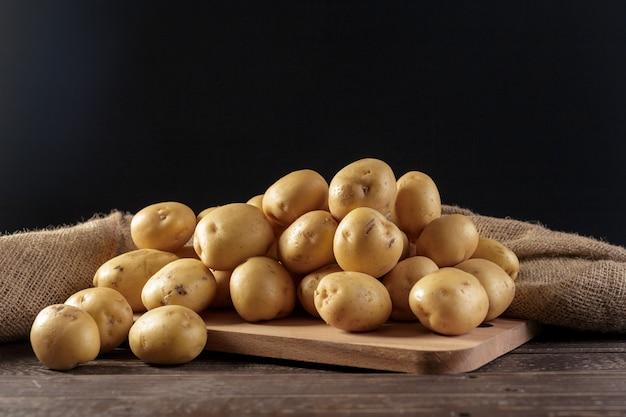Pommes de terre fraîches sur le fond de bois Photo Premium