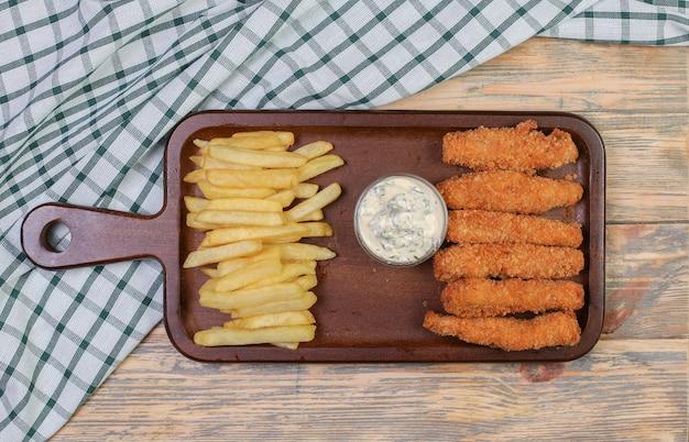 Pommes de terre frites et bâtonnets de poulet avec sauce blanche. Photo gratuit