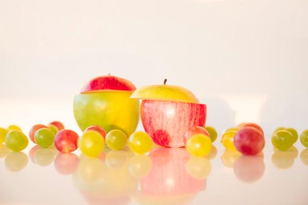 Pommes tranchées de différentes couleurs avec des raisins rouges et verts sur un bureau réfléchissant Photo gratuit