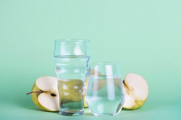 Pommes vertes et arrangement de verres de tailles différentes Photo gratuit
