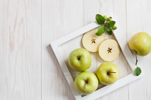Pommes Vertes Dans Un Cadre Blanc Sur Un Fond En Bois Blanc. Photo Premium