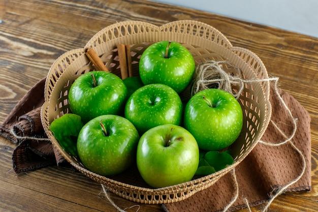 Pommes Vertes, Dans, A, Panier, à, Bâtons Cannelle, Corde, Torchon, Feuilles, Haute Vue Angle, Sur, Table Bois Photo gratuit